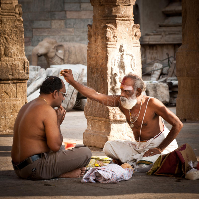 Hindu Brahmin with religious attributes blessing people at Meenakshi Temple. India, Madurai, Tamil Nadu. MADURAI, INDIA - FEBR 16: Hindu Brahmin with religious stock photo