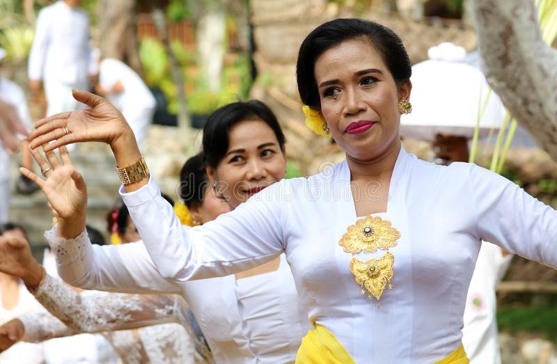 Hindu celebration at Bali Indonesia, religious ceremony with yellow and white colors, woman dancing. Culture dance royalty free stock photo