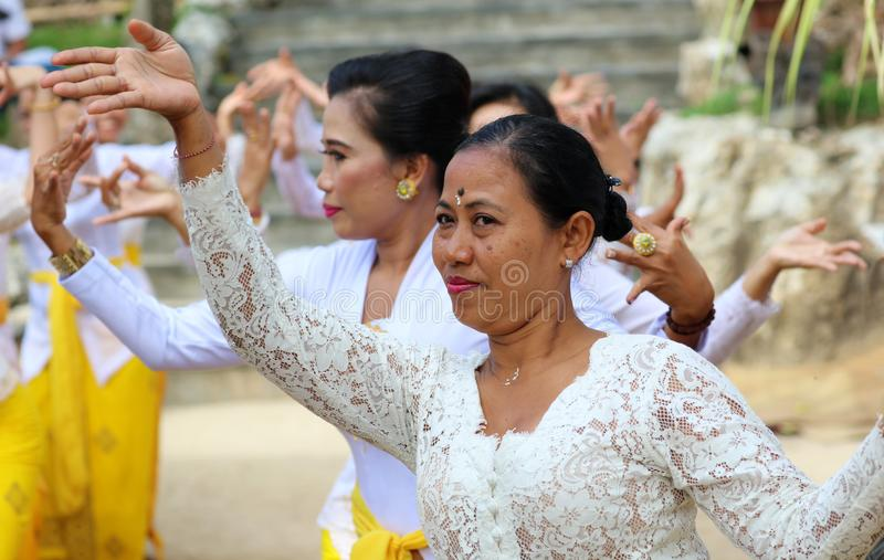 Hindu celebration at Bali Indonesia, religious ceremony with yellow and white colors, woman dancing. Culture dance stock photography
