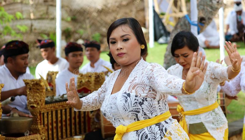 Hindu celebration at Bali Indonesia, religious ceremony with yellow and white colors, woman dancing. Culture dance stock image