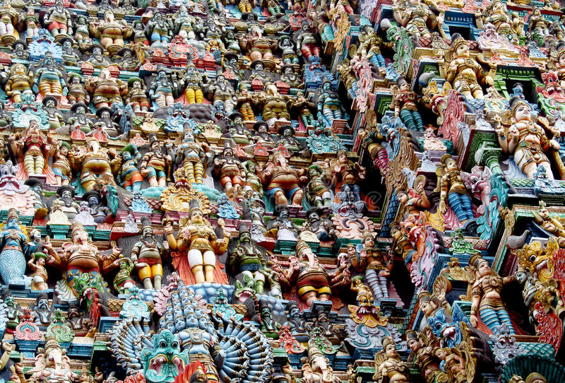 Hindu colorful Gods statues in India. Colored statue on the wall in front of the entrance to the hindu temple with ornament and decorations. Man and woman figure stock image