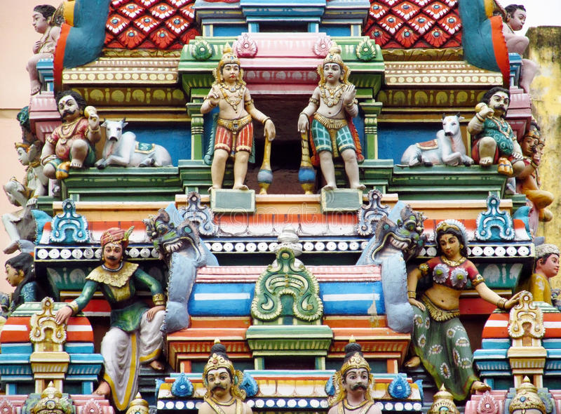 Hindu colorful statues in India. Colored statue on the wall in front of the entrance to the hindu temple with ornament and decorations. Man and woman figure stock photography