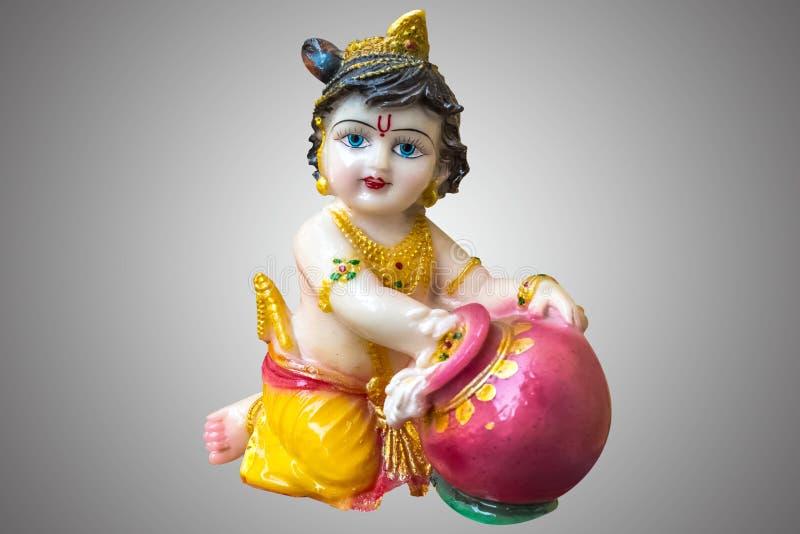 Hindu God Krishna in childhood Gopal isolated in gray background. Hindu God Krishna in childhood Gopal porcelain statuette isolated in gray background stock photo