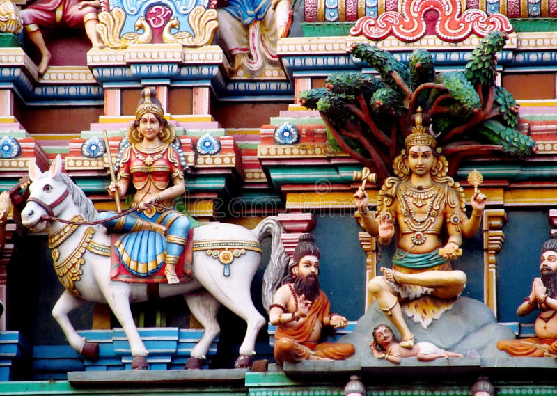 Hindu god mystical statue. Colored statue on the wall in front of the entrance to the hindu temple with ornament and decorations. Man and woman figure, statues stock images
