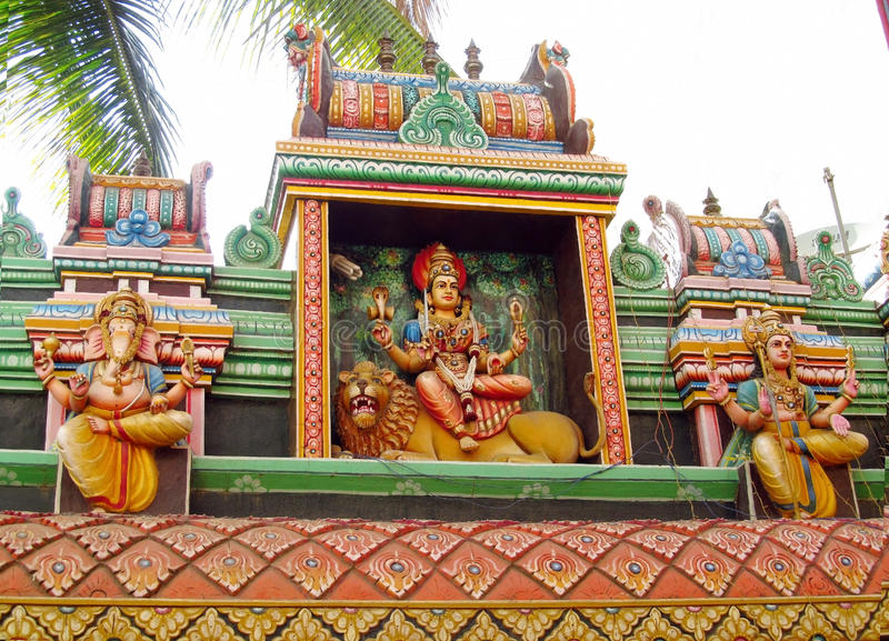 Hindu god statue. Colored statue on the wall in front of the entrance to the hindu temple with ornament and decorations. Man and woman figure, statues of hindu stock images