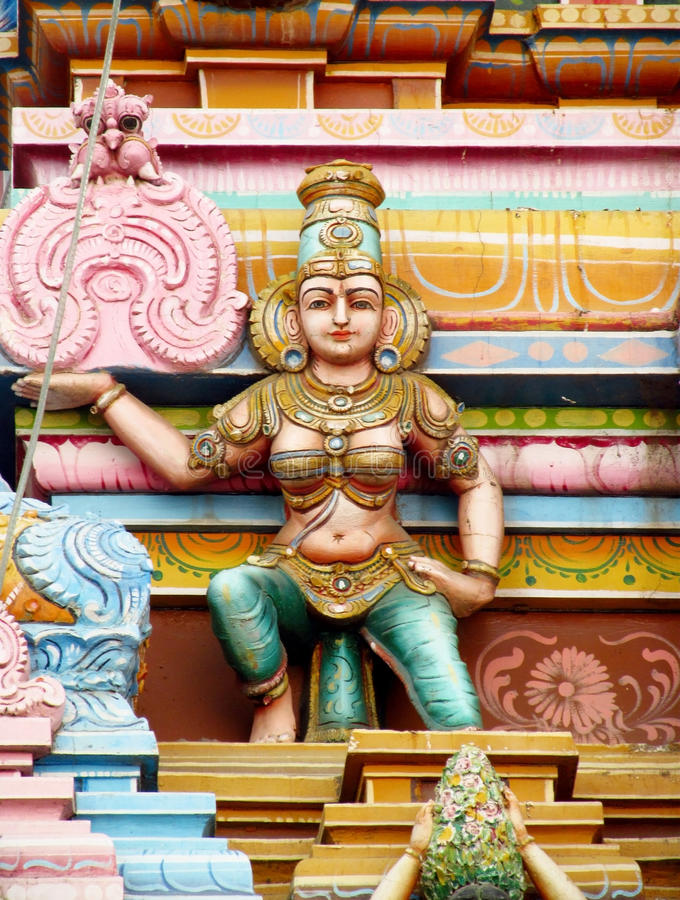 Hindu god statue. Colored statue on the wall in front of the entrance to the hindu temple with ornament and decorations. Man and woman figure, statues of hindu stock photography