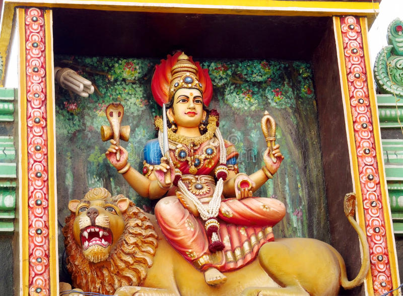 Hindu god statue and lion. Colored statue and lion on the wall in front of the entrance to the hindu temple with ornament and decorations. Man and woman figure stock image