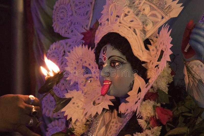 An hindu goddess idol is getting worshipped. A hindu goddess idol, named mother `Kali`is getting worshiped by a priest at midnight stock photos