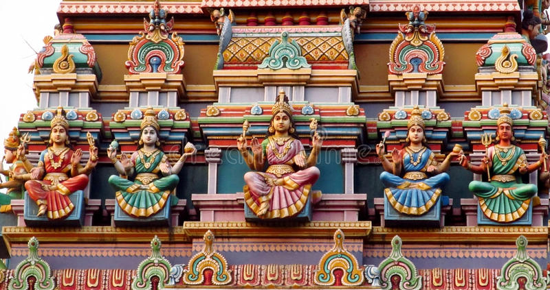 Hindu godess statues. Colored statue on the wall in front of the entrance to the hindu temple with ornament and decorations. Man and woman figure, statues of stock photo