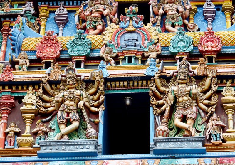 Hindu gods mystical statues. Colored statue on the wall in front of the entrance to the hindu temple with ornament and decorations. Man and woman figure, statues stock images