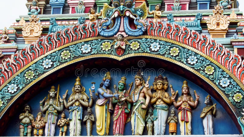 Hindu Gods statues. Colored statue on the wall in front of the entrance to the hindu temple with ornament and decorations. Man and woman figure, statues of hindu royalty free stock image