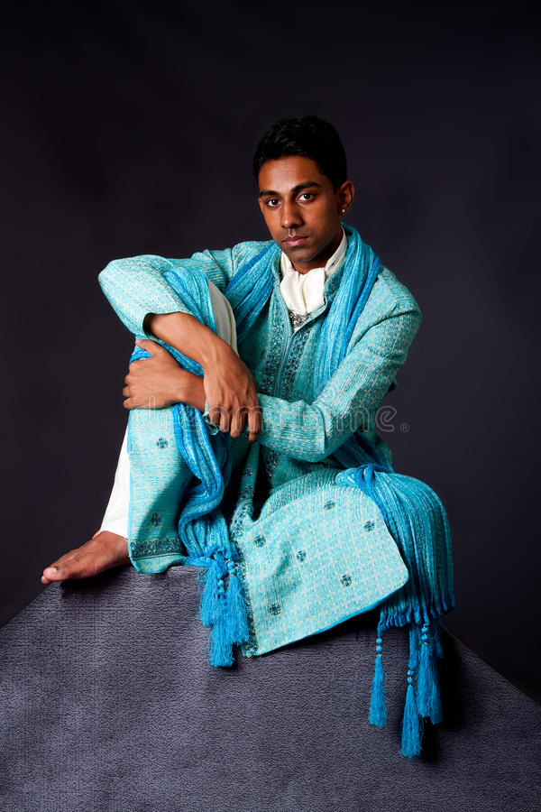 Hindu man sitting on rock. Beautiful authentic Indian hindu man in typical ethnic groom attire sitting relaxed on top of rock leaning on knee. Bengali male royalty free stock photo