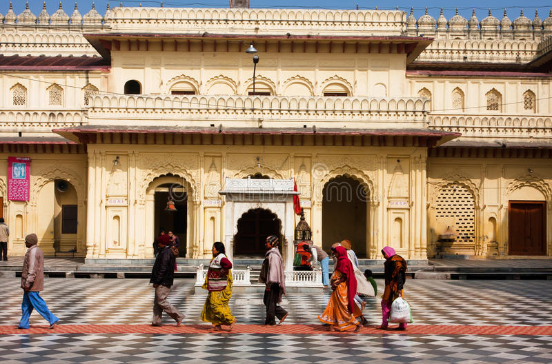 Hindu people rush past the entrance of the yellow wall temple stock images