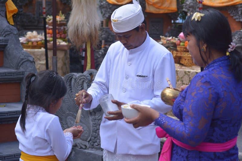 Hindu präst välsignad Balinesisk familj som firar Galungan Kuningan-semester på Bali Indonesien royaltyfri fotografi