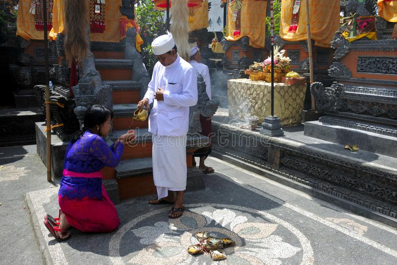 Hindu priest blessing Balinese family celebrating Galungan Kuningan holidays in Bali Indonesia. Hindu priest blessing Balinese family celebrating Galungan stock image