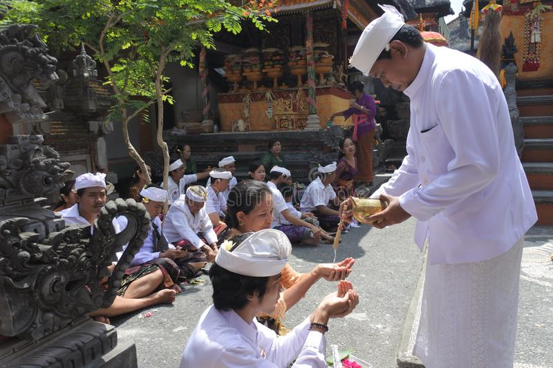 Hindu priest blessing Balinese family celebrating Galungan Kuningan holidays in Bali Indonesia. Hindu priest blessing Balinese family celebrating Galungan stock photos