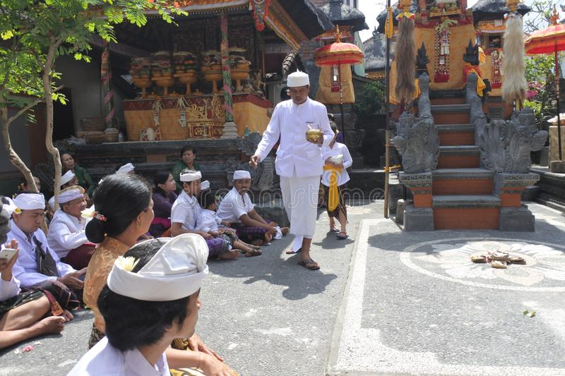 Hindu priest blessing Balinese family celebrating Galungan Kuningan holidays in Bali Indonesia. Hindu priest blessing Balinese family celebrating Galungan royalty free stock images