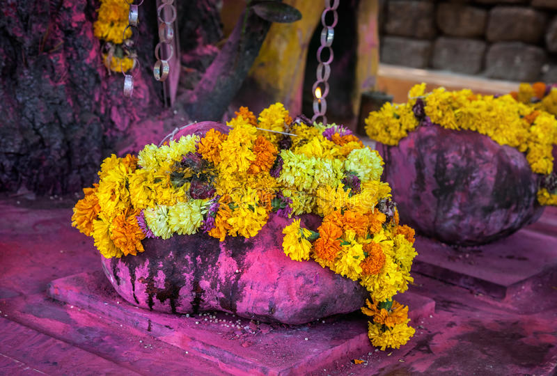 Hindu temple in Goa. Purple stone with Saffron flower garlands in the Hindu temple near Arambol beach, Goa, India royalty free stock images