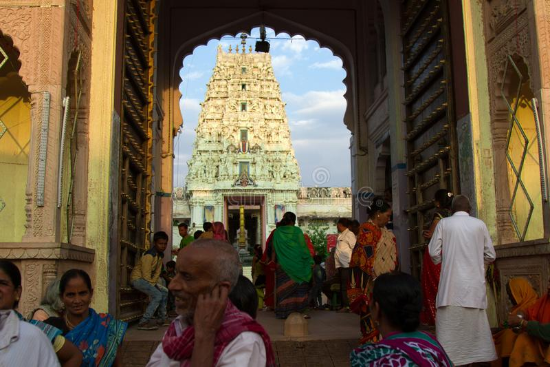 Hindu temple, Mandir and many pilgrims. India, Pushkar-March 4, 2018: Hindu temple, Mandir in the arch of entrance in the frame and many pilgrims on the square royalty free stock photo