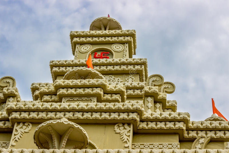 Hindu temple shrine, roof dome. Top spire above the shrine of a Hindu temple with the holy flag on top of a temple dome roof royalty free stock photo