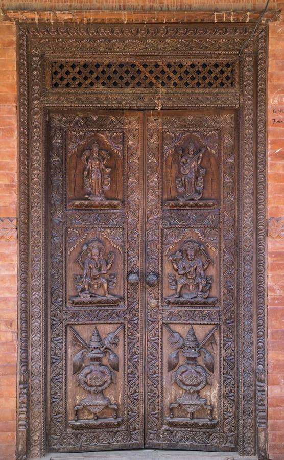 Hindu temple wooden door in Bhaktapur Nepal. Hindu temple wooden door in Bhaktapur, Nepal. Carved decoration and figures of hindu gods royalty free stock photos