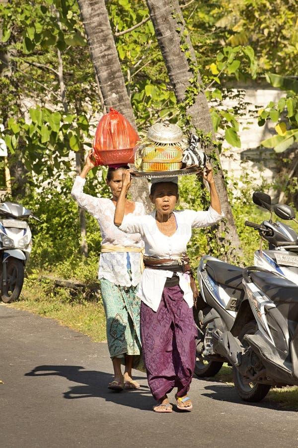 Hindu women bring gifts, in - Nusa Penida, Indonesia royalty free stock images