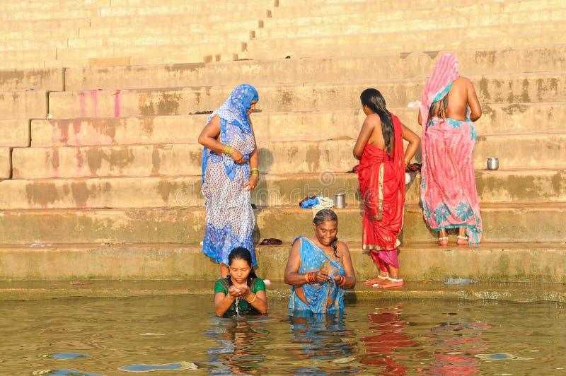 Hindu women taking a ritual bath in the holy Ganges River stock photos