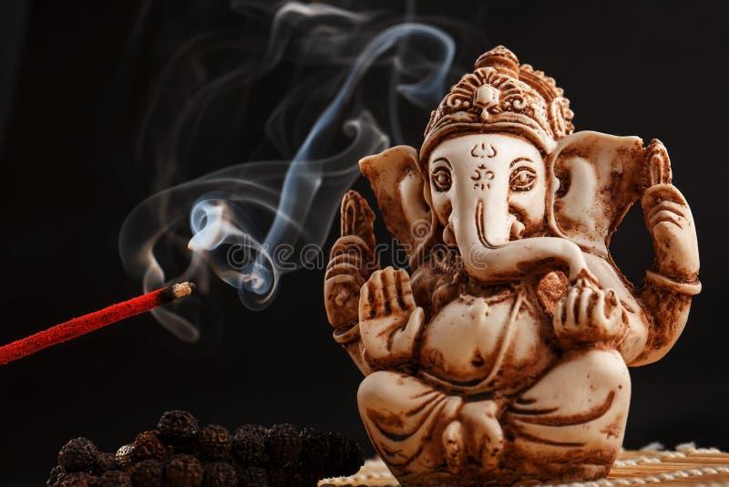 Hinduisk gud Ganesh på en svart bakgrund Rudraksha staty och radband på en trätabell med en röd rökelsepinne- och rökelserök arkivbilder