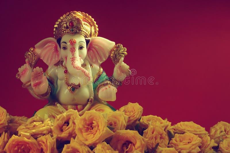 Hinduisk gud Ganesha med rosblomman royaltyfri foto