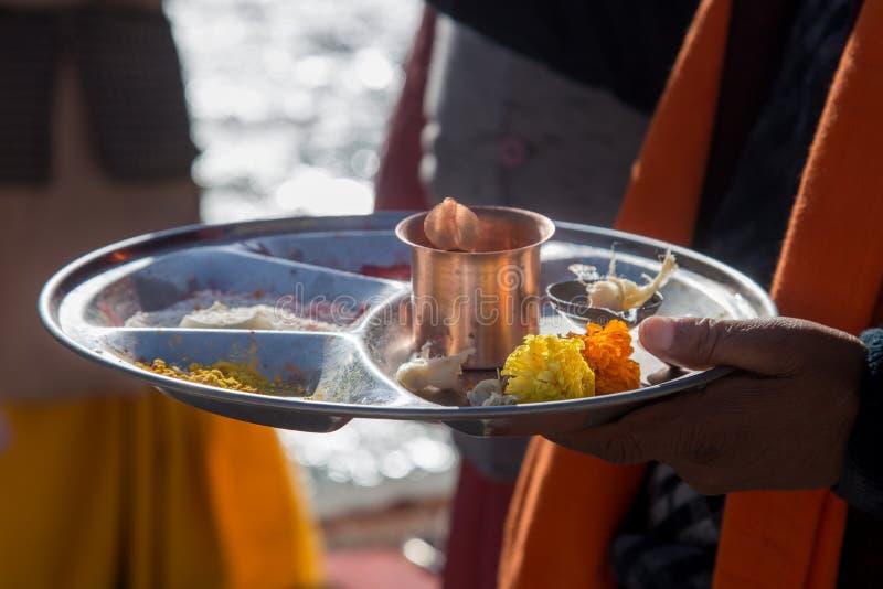 Hinduisk thali för prästinnehavpooja i hand arkivfoto