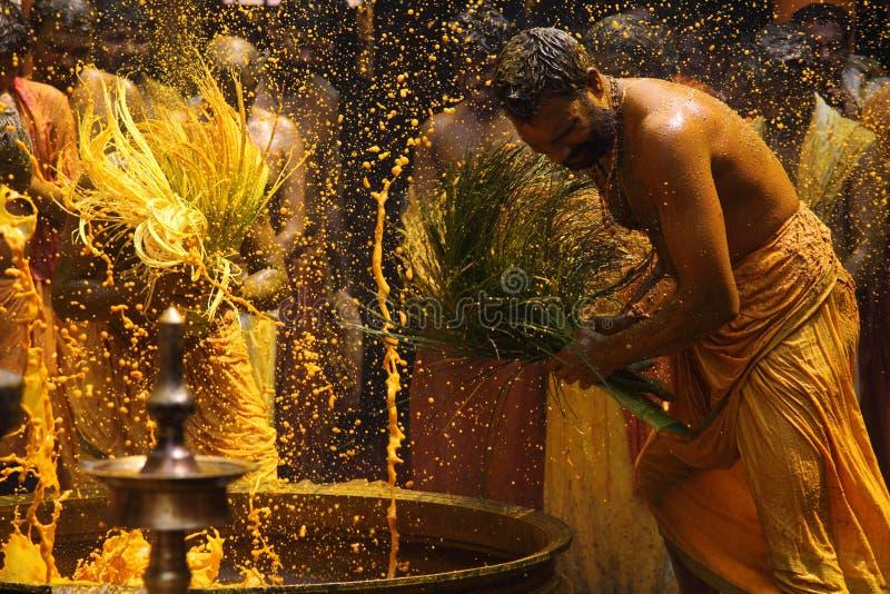 Hinduiska fantaster utför gurkmejabadningritualen under den årliga festivalen som rymms på den Amman templet arkivfoto