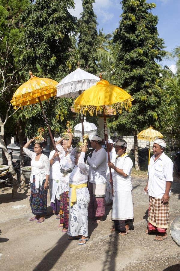 Hinduiska kvinnor bär på deras huvudofferings, - Nusa Penida, Indonesien arkivbilder