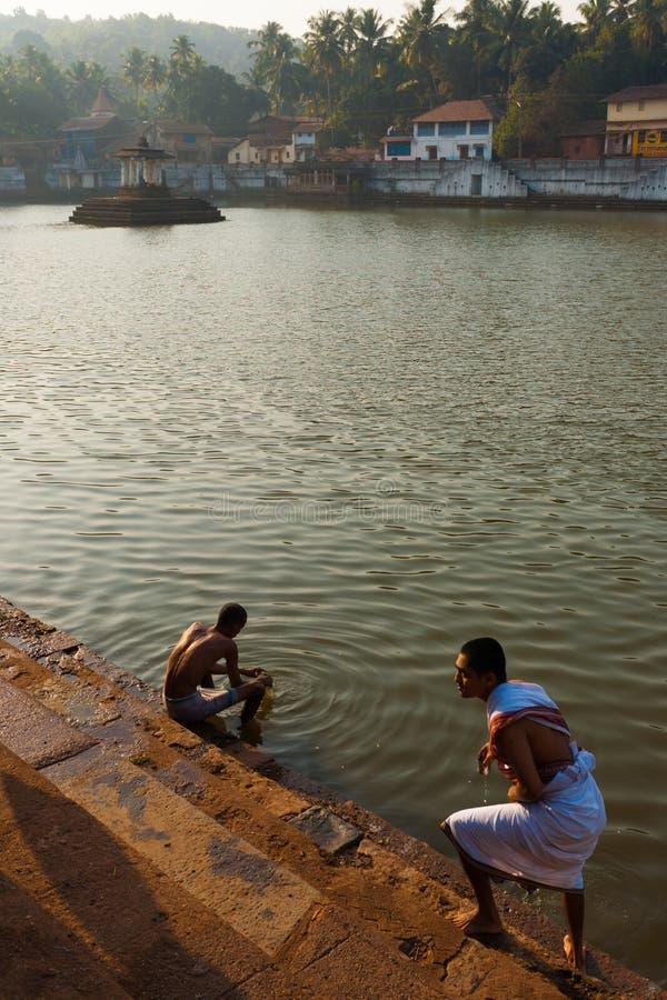 Hinduiska män som badar moment för Gokarna behållarmorgon royaltyfria bilder