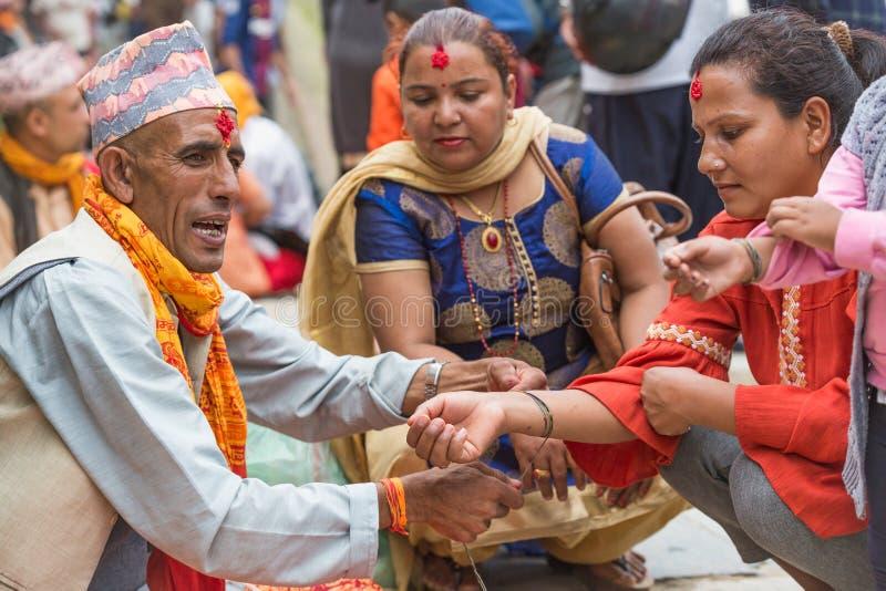 Hinduiska Pople som in mottar Raksha Bandhan på den Pashupatinath templet fotografering för bildbyråer