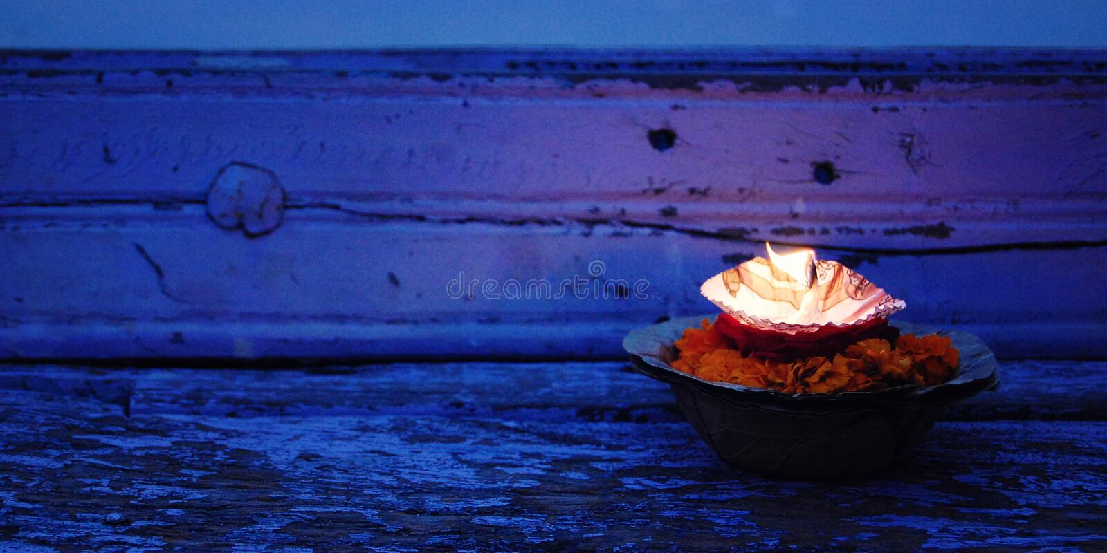 Hinduism religious ceremony puja flowers and candle near river Ganga, Varanasi, Uttar Pradesh, India. Close-up Burning candle and flowers - retro filter royalty free stock photos