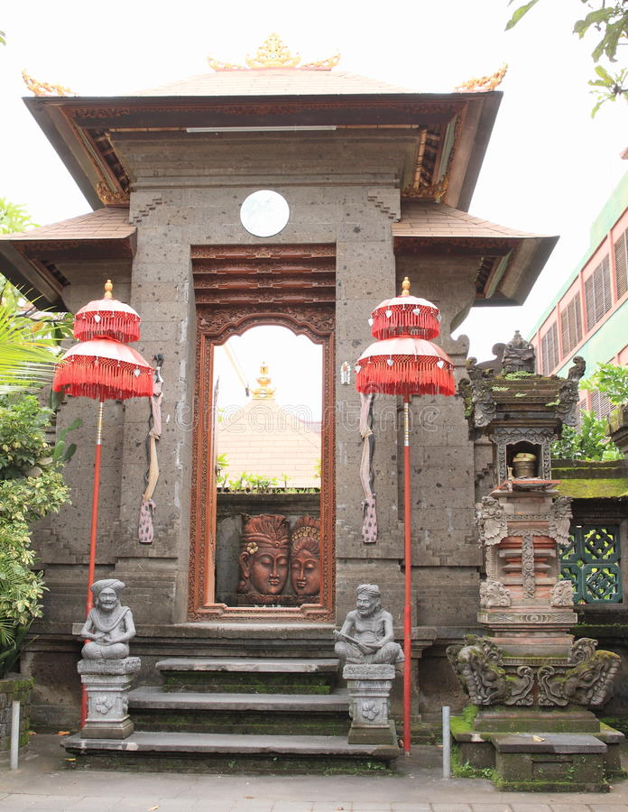 Hinduist temple. With statues, red umbrellas and place of sacrifices in Denpasar Bali, Indonesia royalty free stock photography