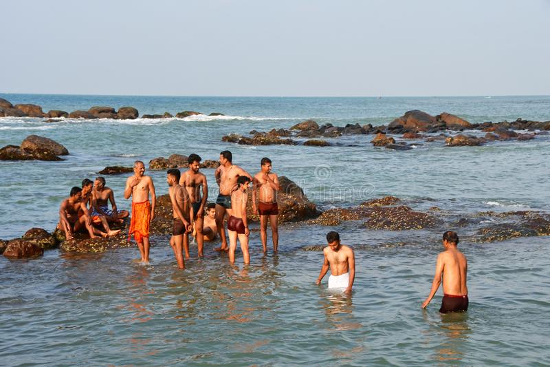 E Hindus在印度洋的水域中沐浴在盖帽 免版税库存图片
