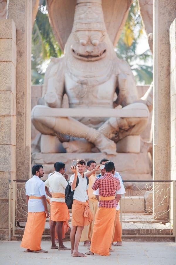Hindus beklär den iklädda apelsinen ställningar framme av Narasimha arkivfoto