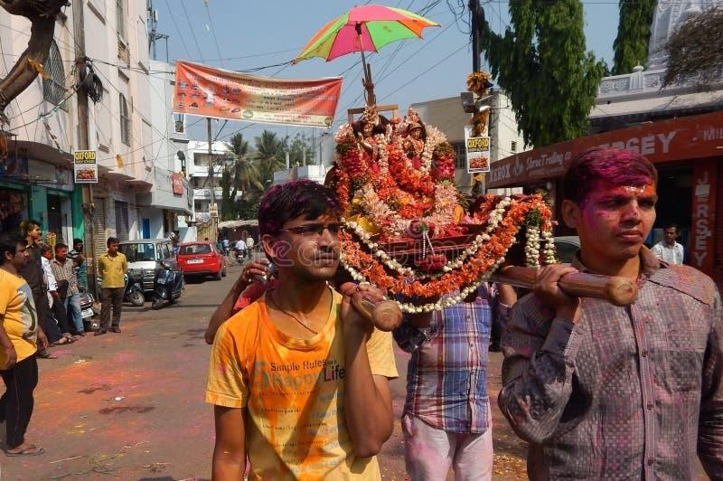 Hindus firar den Holi festivalen tar bärande förebilder för procession royaltyfri fotografi