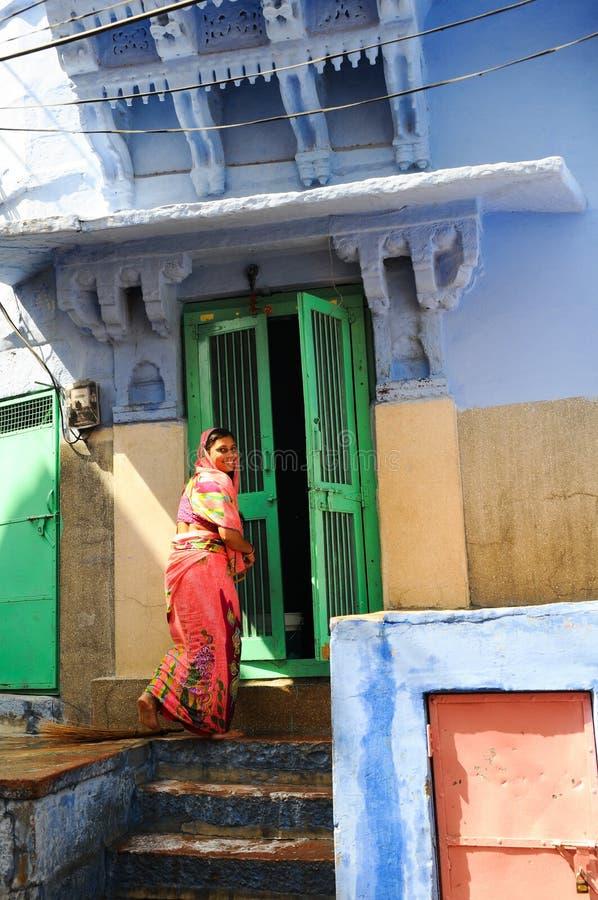 Hinduska kobieta w sari uśmiecha się przed kolorowym domem zdjęcia royalty free