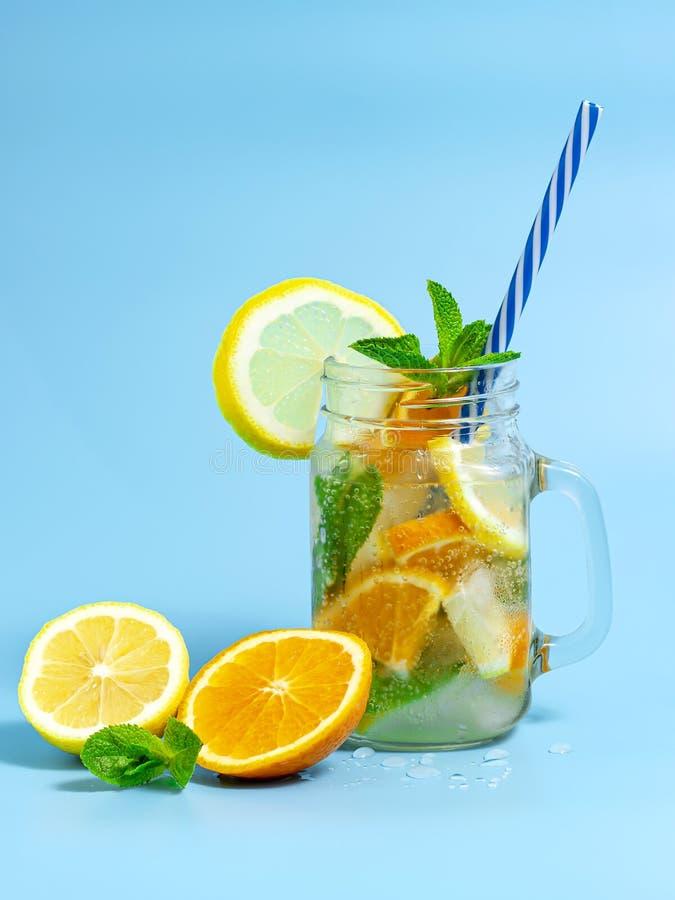 Hineingegossenes Detoxwasser mit Eis-, Zitronen- und Orangenscheiben mit Minze auf blauem Hintergrund Gefrorenes kaltes Sommercoc lizenzfreies stockfoto