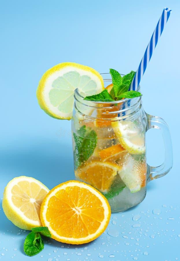 Hineingegossenes Detoxwasser mit Eis-, Zitronen- und Orangenscheiben mit Minze auf blauem Hintergrund Gefrorenes kaltes Sommercoc stockfotos