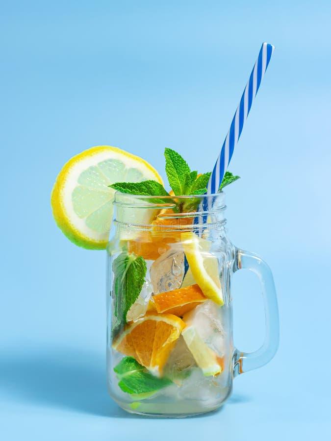 Hineingegossenes Detoxwasser mit Eis-, Zitronen- und Orangenscheiben mit Minze auf blauem Hintergrund Gefrorenes kaltes Sommercoc lizenzfreies stockbild