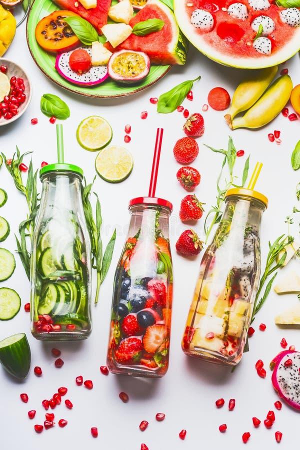 Hineingegossenes Wasser in den Flaschen mit frischen Früchten, Gemüse und Kräutern auf weißem Hintergrund mit Bestandteilen lizenzfreies stockbild