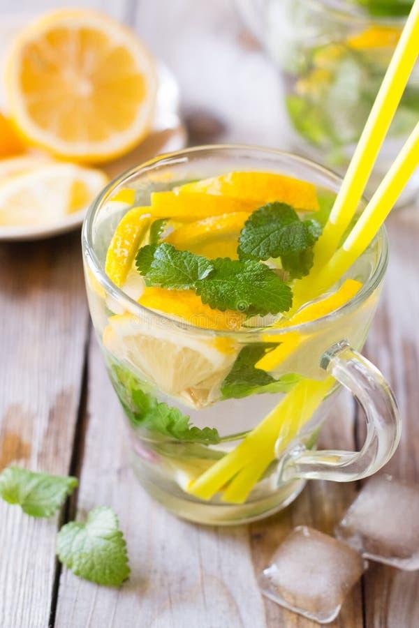Hineingegossenes Wasser mit Zitrone und Rosmarin stockfotos