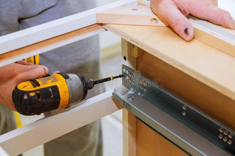 Hinge drawers assembly on kitchen cabinet door. Hinge assembly on kitchen cabinet drawers carpenter with screwdriver assembling screwing furniture repair home stock photo