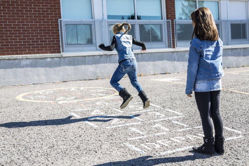 Hinkelspels op het schoolplein met vriendenspel samen royalty-vrije stock afbeeldingen