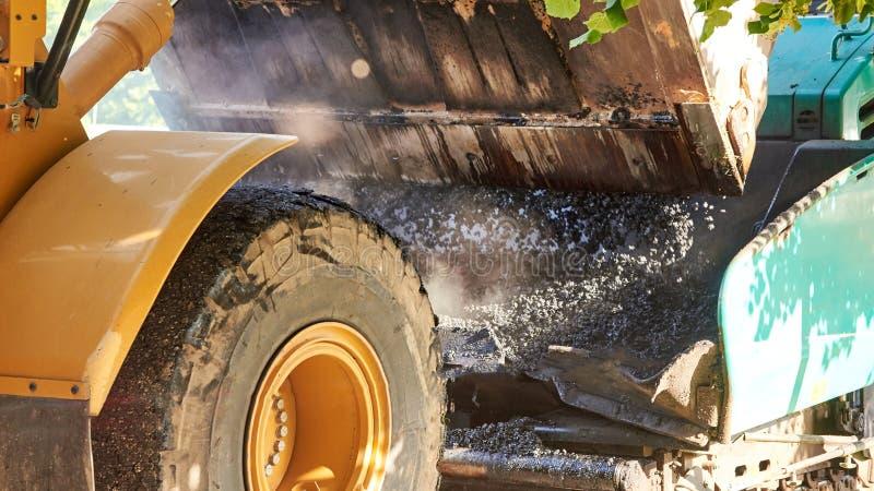 Hinktraktoren häller varm asfalt in i en väghyvel, konstruktion av en ny väg, material för närbild för vägkonstruktion royaltyfri foto