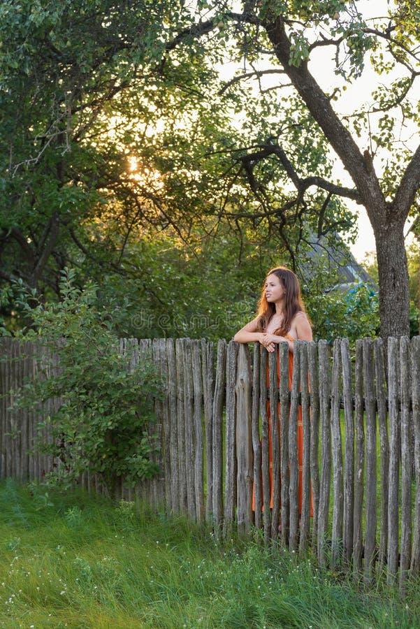 Hinter einem ländlichen Zaun ist eine einsame junge Frau in einem Dorfkleid an der Dämmerung lizenzfreies stockbild
