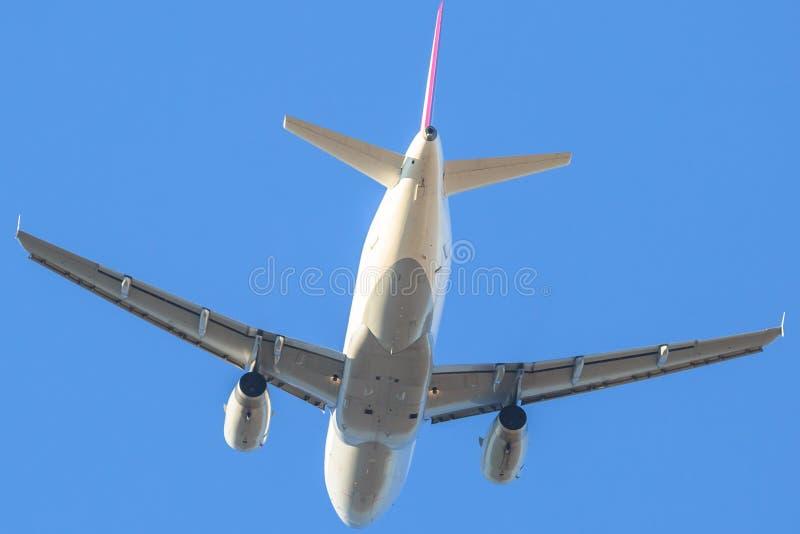 Hinter weißem Flugzeug im Himmel lizenzfreies stockbild